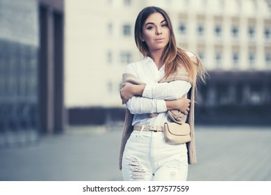 Happy young fashion woman walking on city street Stylish female model with belt bag in white shirt and ripped jeans