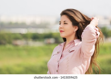 Happy young fashion woman walking outdoor  Stylish female model with long brown hairs in light pink shirt