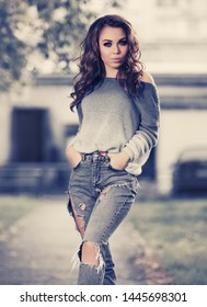 Happy young fashion woman walking on city street Stylish female model in ripped jeans and gray blue ullover