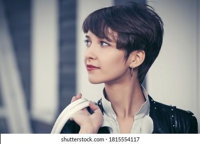 Fröhliche junge Modefrau, die auf der Stadtstraße spazieren geht Stilweibliches Modell in schwarzer Lederjacke mit pixigem Haar