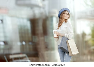 Happy young fashionable woman with bags having a coffee break after shopping and holding take away coffee against urban background.