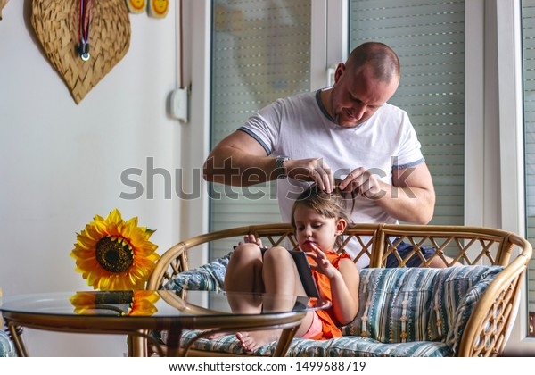 Happy young father braiding daughter hair. Three years old girl enjoying time with her dad, while watching cartoons on tablet. Bearded man and cute little girl at home, making creative hairstyle.