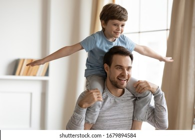 Happy young father carry on back have fun feel playful with little preschooler son at home, smiling dad playing with excited small boy child, relax on weekend together entertaining indoors