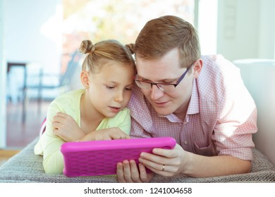 Happy young father have fun with his pretty little daughter during working with tablet at home on couch