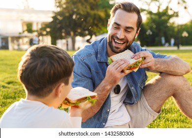 Happy young father having a picnic with his little son at the park, eating sandwiches