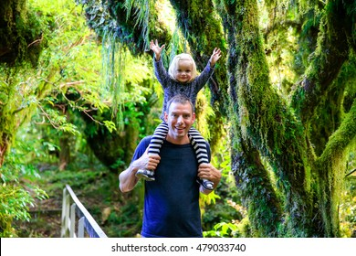 Happy young father with his daughter in Rain forest .Trailing moss and gnarled trees, Egmont National Park, Taranaki, North Island, New Zealand
