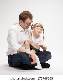 Happy young father with his smiling daughter, neutral background