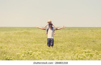 Happy young father holding his little daughter on shoulders against summer meadow
