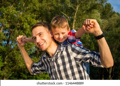 Happy young father holds his son piggyback ride on his shoulders and looking up. Little boy is sitting piggyback on shoulders his dad while imitating the flight