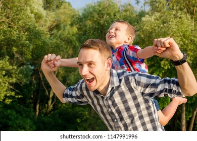 Happy young father holds his son piggyback ride on his shoulders, looking up and laughing. Little boy is sitting piggyback on shoulders his dad while imitating the flight
