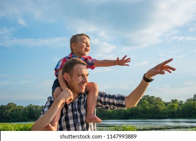 Happy young father holds his son piggyback ride on his shoulders, points at something with his hand and laughing. Little boy is sitting piggyback on shoulders his dad at river background