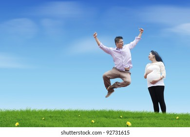 A happy young father jumping on the meadow with his pregnant wife