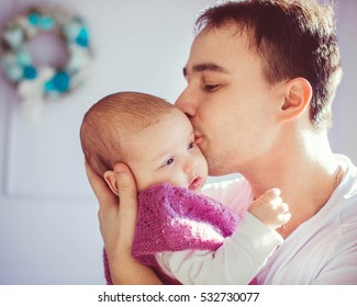 happy and young father kiss his cutie small babygirl