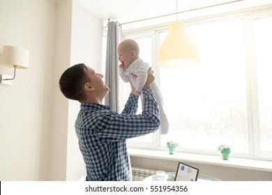 Happy young father lifting cute baby up high in the air near the working place with laptop, spending and enjoying time together, working at home, freelancer, having freedom and family time concept