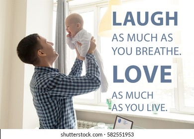 """Happy young father lifting cute baby up high in the air near the working place with laptop. Photo with motivational text """"Laugh as much as you breathe. Love as much as you live"""". Square image"""