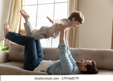 Happy young father lifting small preschool kid son, pretending to fly as plane in living room. Energetic little child boy having fun with strong daddy, involved in funny game together at weekend time.