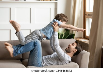 Happy young father lying on cozy sofa, lifting playful little child son at home. Excited two male generations family having fun playing together, enjoying weekend time together in living room.