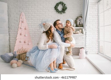 Happy young father mother and baby boy in christmas decorated studio