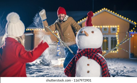 Happy Young Father, Mother and Cute Little Daughter Play in Snowballs around the Snowman They've Build in the Backyard of Their Idyllic House Decorated with Garlands. Family Spends Time Together.