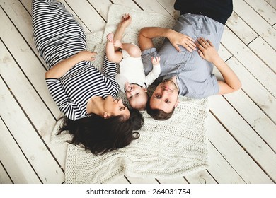Happy young father, mother and cute baby boy lying on rustic wooden floor