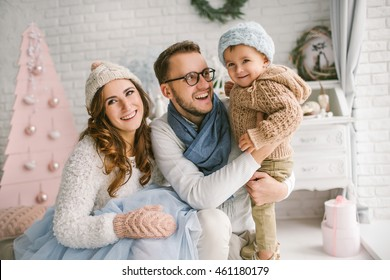 Happy young father, mother and cute baby smiling in bright loft studio