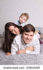 Happy young father, mother, little son lies on bed in bedroom, focus on man