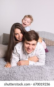 Happy young father, mother, little son lies on bed in bedroom