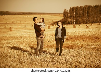Happy young father and mother with two year old baby girl walking in harvested field