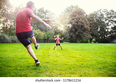Happy young father play with his little son football in green sunny park