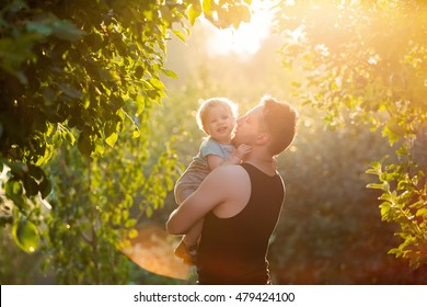 Happy young father playing with his littlte baby son on sunshine warm autumn or summer day. Beautiful sunset light in the apple garden or in the park. Happy family concept