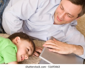 happy young father playing with his son with laptop