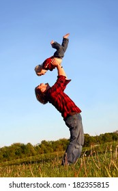 Happy young father is raising his young child up in the air over his head as they play outside on a sunny summer day.