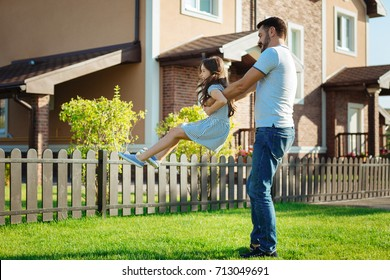 Happy young father spinning his little daughter