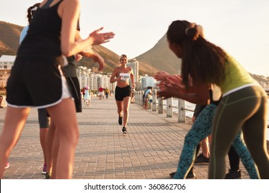 Happy young female athlete being applauded by supporters as she reaches the finishing line of a running race. Young people encouraging race runners outdoors in the city.