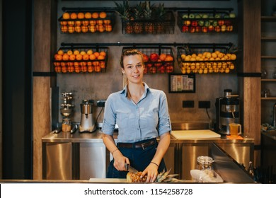 Happy young female bartender standing at juice bar counter and working.