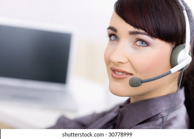 Happy young female customer service operator talking on headset, sitting in front of computer screen, smiling.