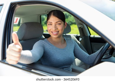 happy young female driver giving thumb up inside a car