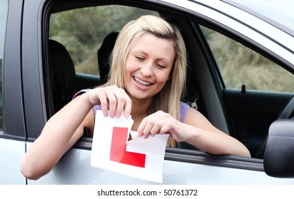 Happy young female driver tearing up her L sign sitting in her car