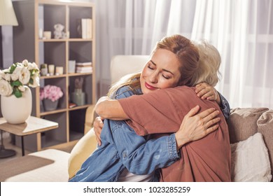 Happy young female embracing mother while locating in living room. Cuddle concept