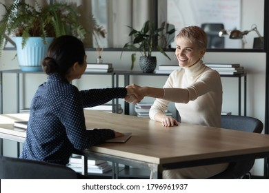 Happy young female employer handshaking with smiling indian job candidate, welcoming at interview in office. Two smiling diverse businesswomen celebrating establishing international cooperation.