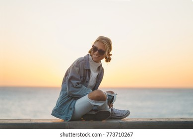 Happy young female enjoying the sunset. Cheerful and happy. Hipster girl by the sea in sunset light.