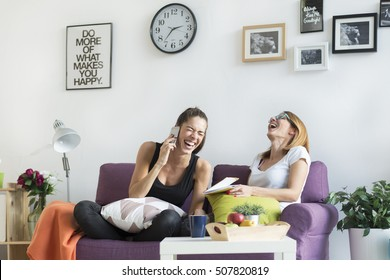 Happy young female friends conversing in the living room at home