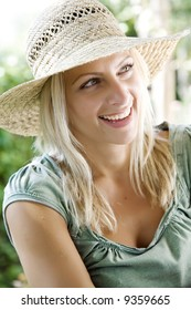 happy young female in her garden wearing straw hat