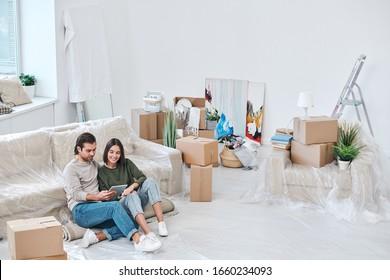 Feliz que una joven y su esposo estén sentados en una alfombra rodada por un sofá y naveguen por la tienda de muebles en línea
