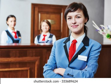 Happy young female hotel receptionist worker standing at reception
