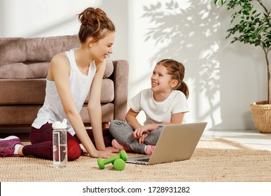 Happy young female and little daughter in sportswear sitting on floor near laptop and watching video tutorial while preparing for workout together at home