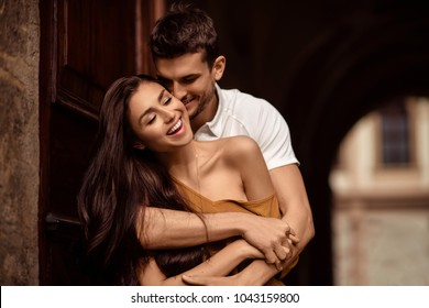 Happy young female with long dark hair glad to recieve passionate kiss from her boyfriend. Handsome male embraces his girlfriend and kisses. Portrait of lovely young couple express mutual love.