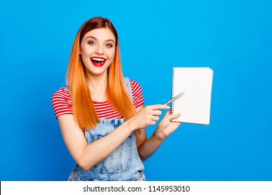 Happy young female student showing by pen on white sheet of paper isolated on colourful vivid blue background