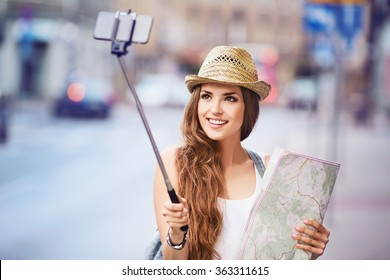 Happy young female tourist with map taking selfie on city street