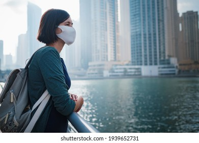 Happy young female traveler with white protective mask in the big city of Dubai, famous place Dubai marina. Luxury and comfortable tourism season in United Arab Emirates. The New Reality and the Norm